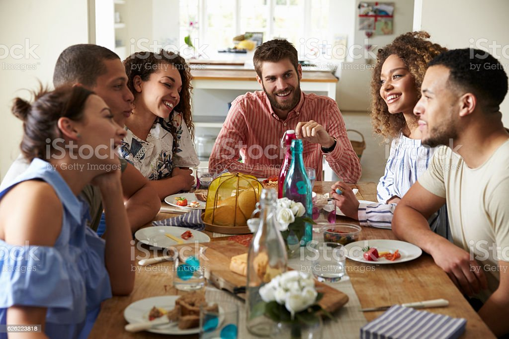Young adults laughing as they talk at a table over - foto de acervo