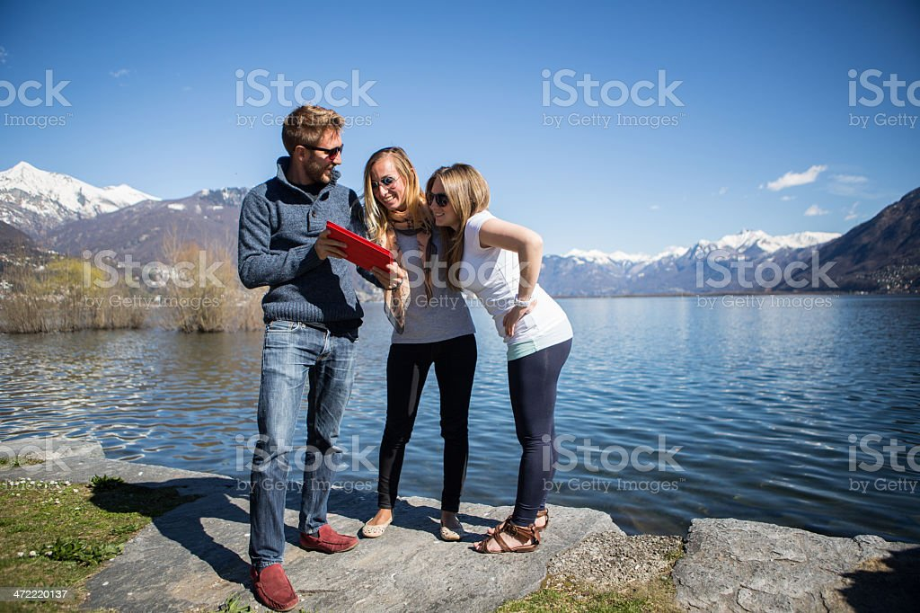 Young adults looking at digital tablet royalty-free stock photo