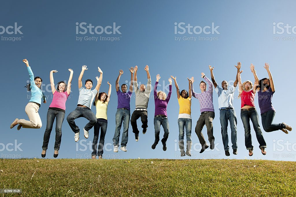 Young Adults A large group of vibrant young adults outside with a sky background   Achievement Stock Photo