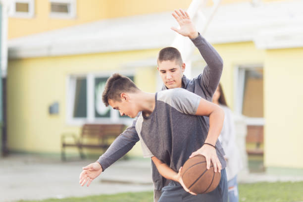Young adults playing basketball stock photo