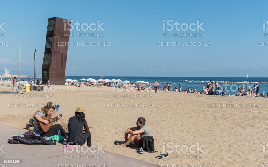 Young adults playing music on Barcelona beach stock photo