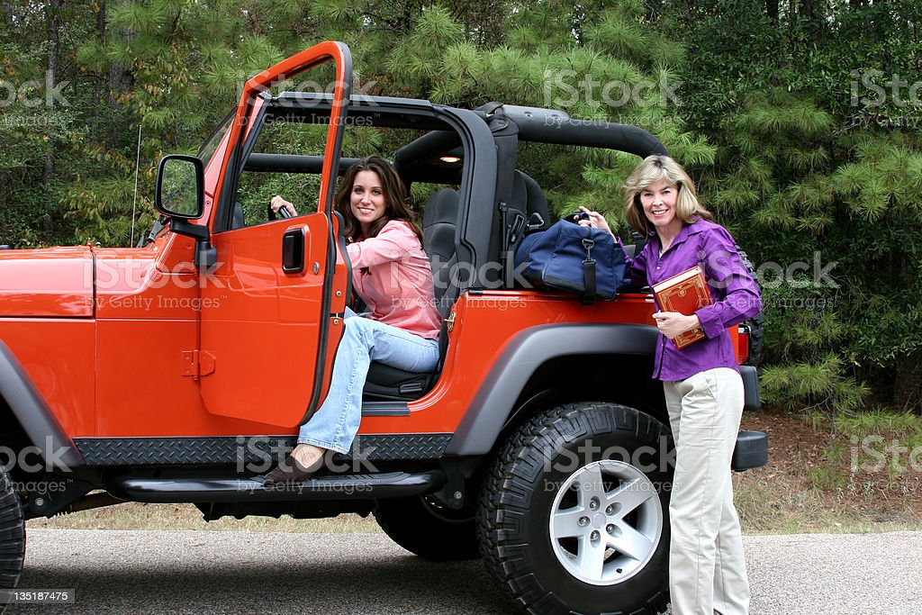 Young adults ready to leave in jeep royalty-free stock photo