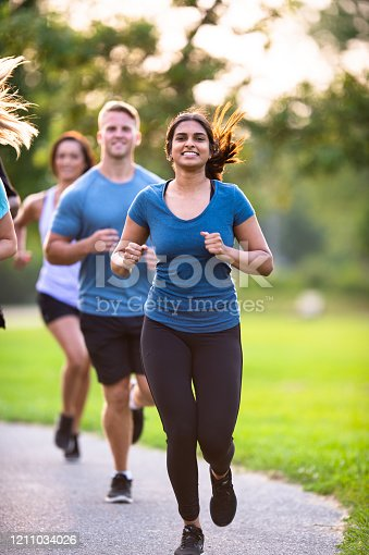A group of multi-ethnic young adults run outside together on a sunny summer day.  They are each wearing comfortable active wear and smiling as they enjoy their time together.