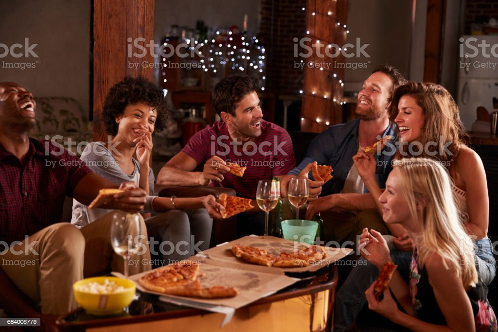 Young adults sharing pizzas at a party at home - foto de stock