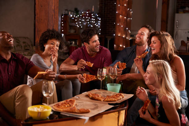 Young adults sharing pizzas at a party at home - foto de acervo