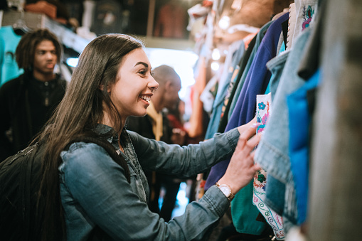 A smiling group of young adults have fun shopping for retro and vintage clothing styles at a second hand thrift store.  Mixed ethnic group.  Horizontal image with copy space.