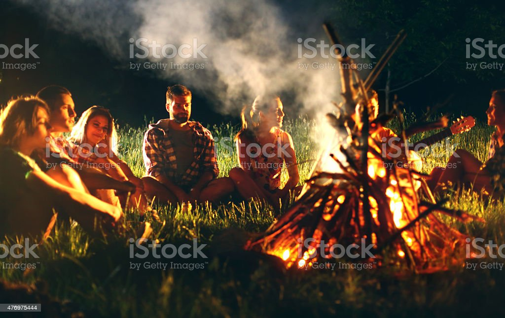 Young adults sitting around campfire. stock photo