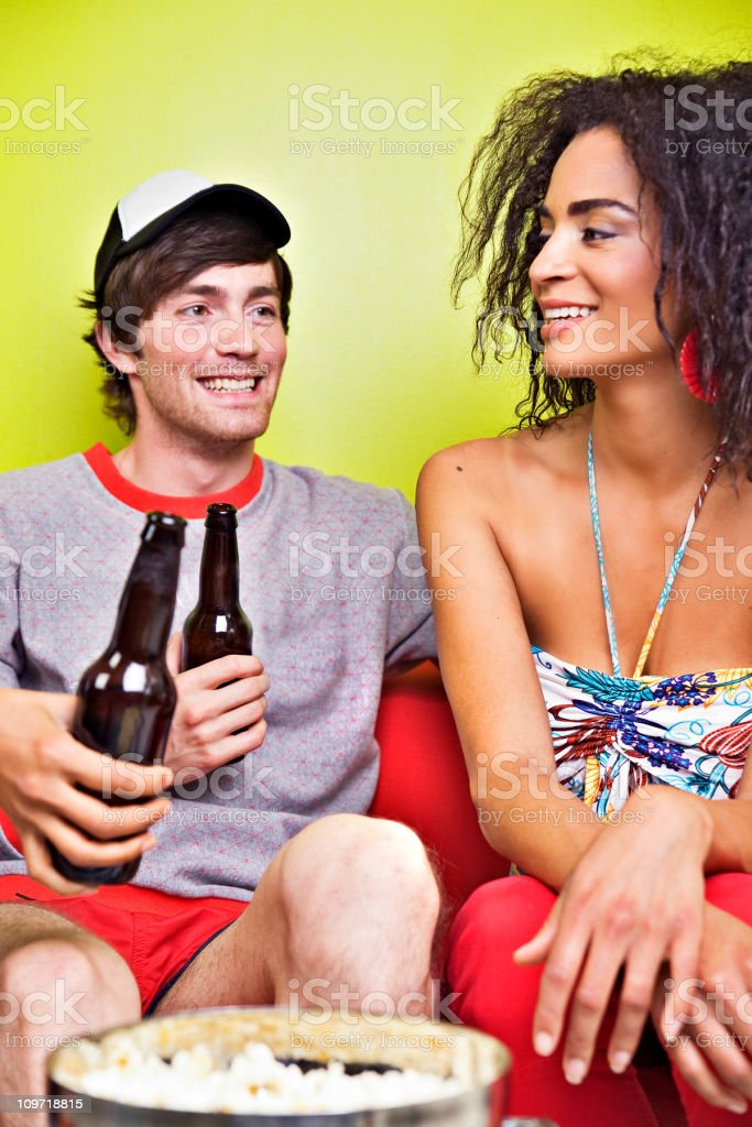 Young Adults Sitting on Couch Drinking Beer royalty-free stock photo