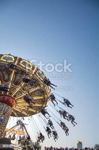 Dallas, Texas USA - October 11, 2015: young adults riding the Swing ride at the Texas State fair as the sun sets on a fun filled day