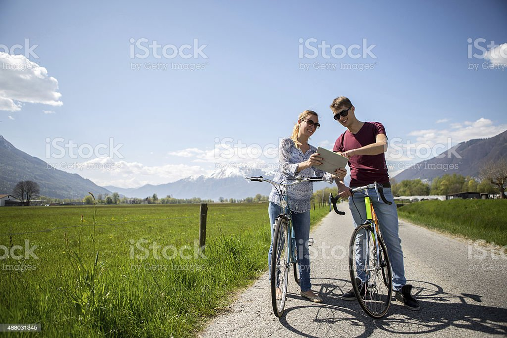 Young adults using digital tablet on bicycles royalty-free stock photo