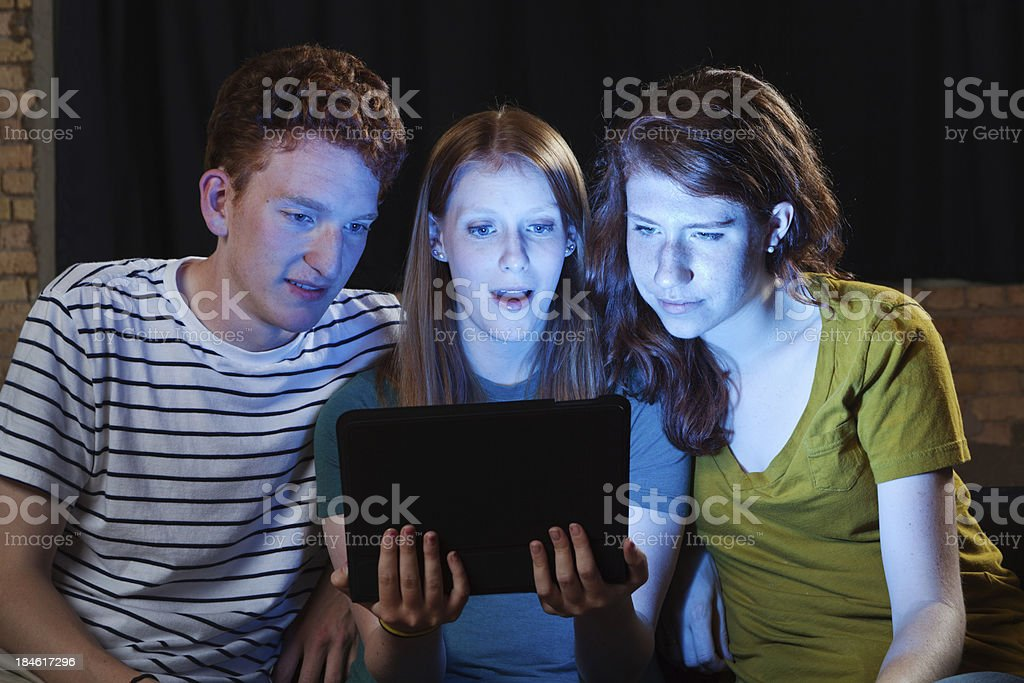 Young Adults Watching Streaming Video Together on Digital Tablet Computer royalty-free stock photo