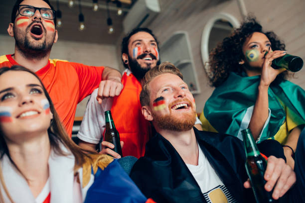 young adults watching world soccer championship on tv and drinking beer - sports championship stock photos and pictures