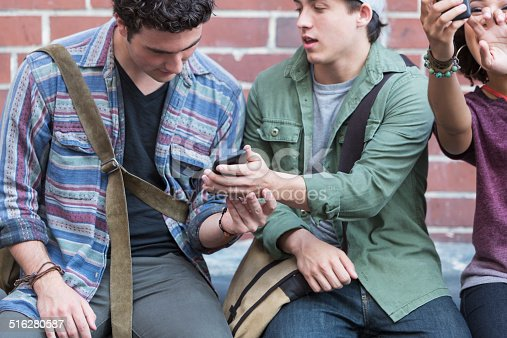 521022435istockphoto Young adults with mobile phones 516280587