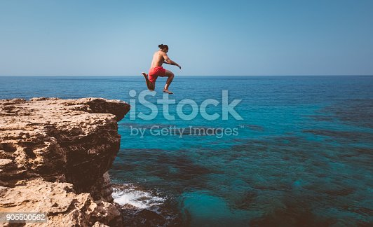 istock Young adventurous diver jumping off cliff into ocean 905500562