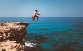 Brave man diving from high cliff into blue sea waters on tropical island summer adventure