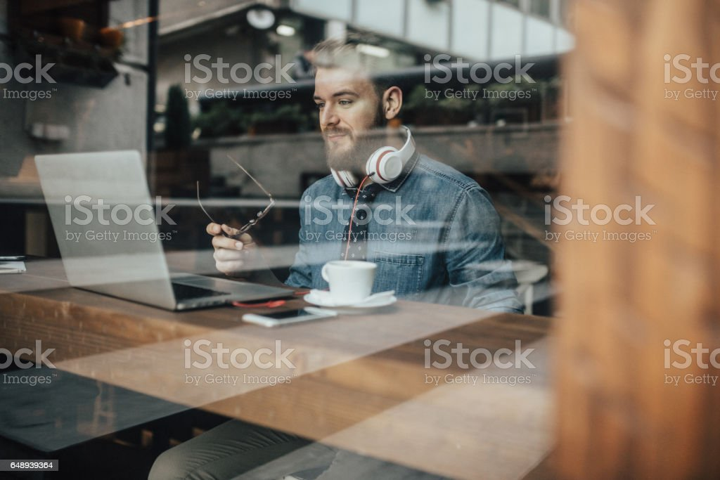 Young advertising art director working on laptop from the coffee shop stock photo