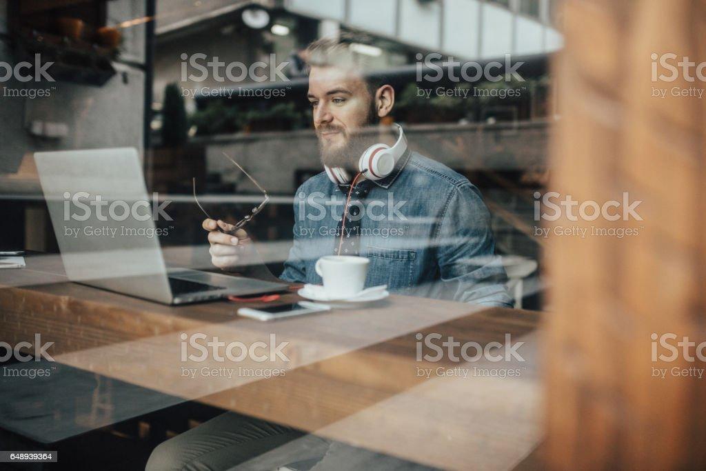 Unga reklam konst-chef som arbetar på laptop från kafé bildbanksfoto