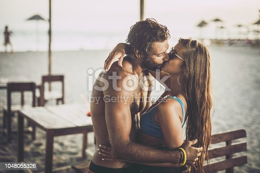 Young loving couple kissing with their eyes closed during summer day on the beach.