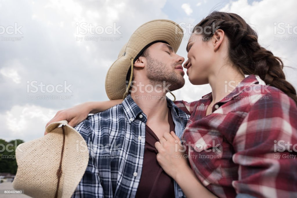 young affectionate cowboy style couple emrbacing and kissing with eyes closed outdoors stock photo