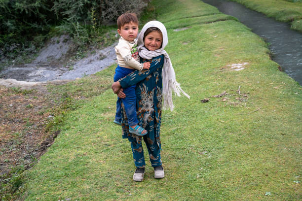 Young Afghani girl with a baby boy in Wakhan Corridor, Afghanistan stock photo