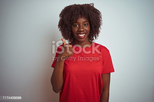 Young african afro woman wearing red t-shirt over isolated white background doing happy thumbs up gesture with hand. Approving expression looking at the camera with showing success.