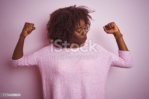 657442382istockphoto Young african afro woman wearing sweater standing over isolated pink background showing arms muscles smiling proud. Fitness concept. 1174408605