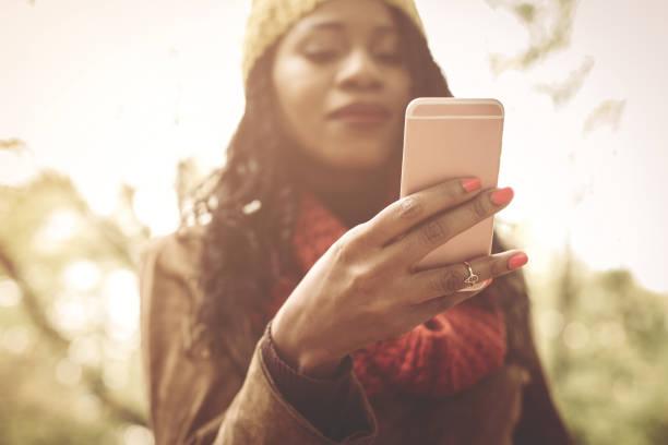 young african america mädchen im park mit smartphone. schwerpunkt liegt auf der hand. - garden types stock-fotos und bilder