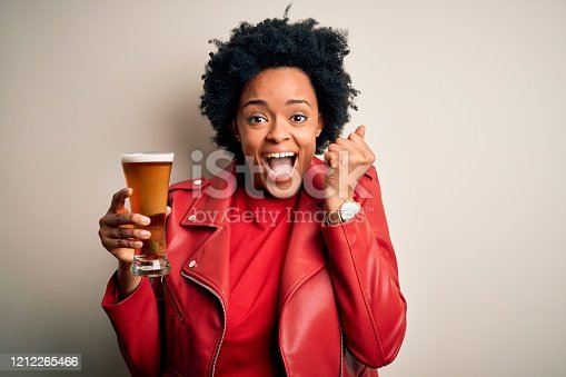 Young African American afro woman with curly hair drinking glass of beer with alcohol screaming proud and celebrating victory and success very excited, cheering emotion