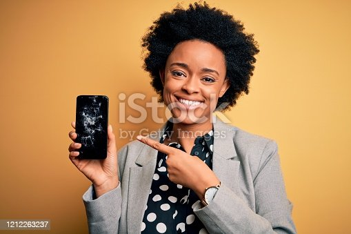 1159261513 istock photo Young African American afro woman with curly hair holding cracked broken smartphone very happy pointing with hand and finger 1212263237