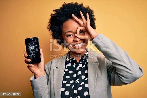 1159261513 istock photo Young African American afro woman with curly hair holding cracked broken smartphone with happy face smiling doing ok sign with hand on eye looking through fingers 1212263258