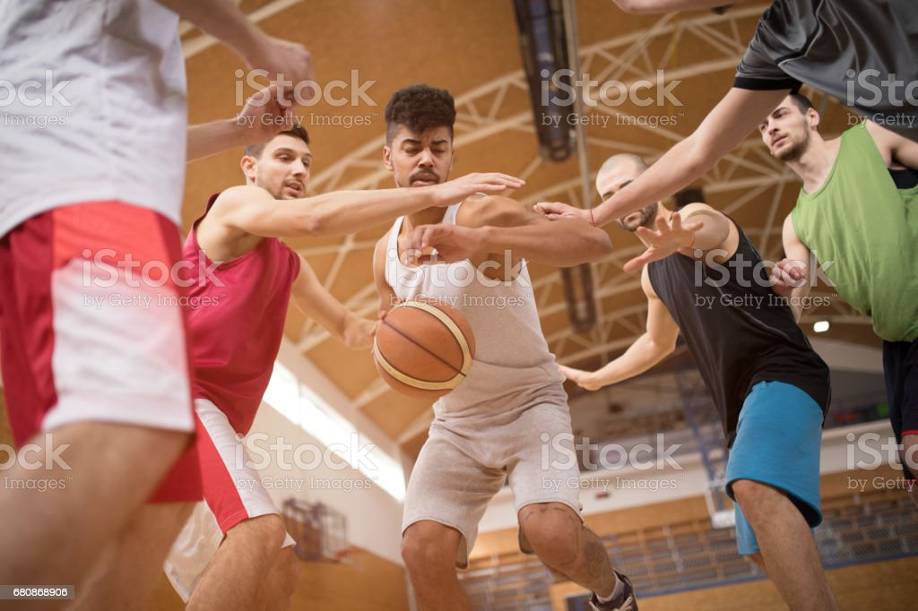 Young African American basketball player trying to avoid his opponents on a match. royalty-free stock photo