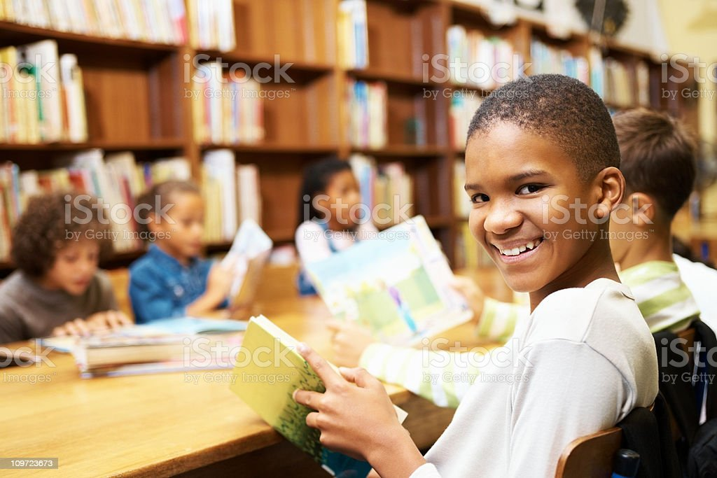Young African American boy studying in school library stock photo