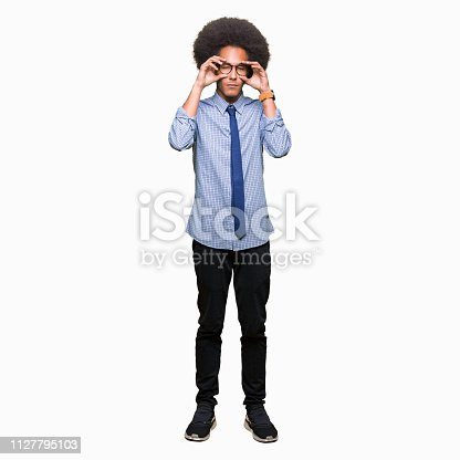 istock Young african american business man with afro hair wearing glasses Trying to open eyes with fingers, sleepy and tired for morning fatigue 1127795103