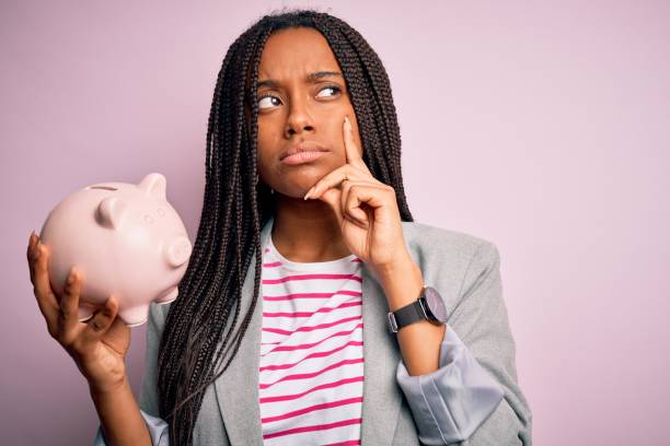 Young african american business woman saving money on piggy bank over isolated background serious face thinking about question, very confused idea stock photo