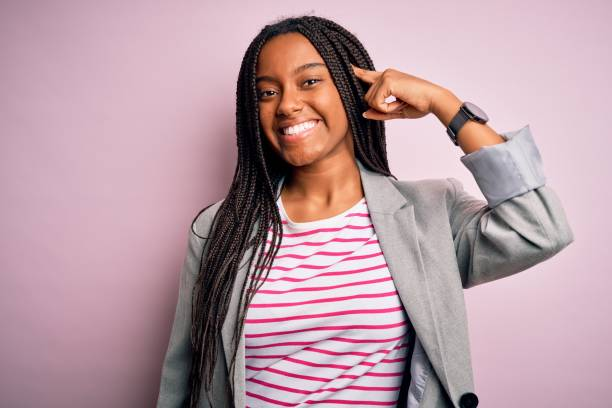Young african american business woman standing over pink isolated background Smiling pointing to head with one finger, great idea or thought, good memory stock photo