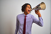 istock Young african american businessman screaming using vintage megaphone 1175453379