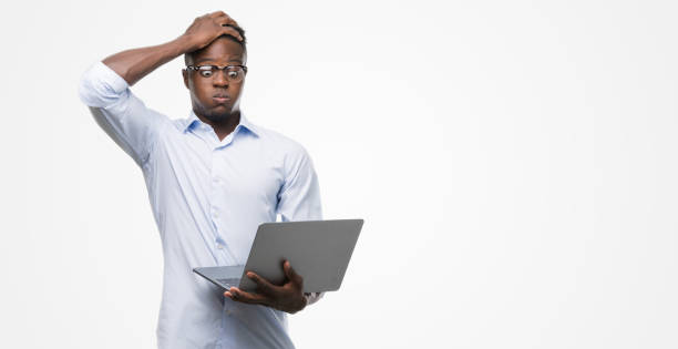 young african american businessman using computer laptop stressed with hand on head, shocked with shame and surprise face, angry and frustrated. fear and upset for mistake. - frustration stock pictures, royalty-free photos & images
