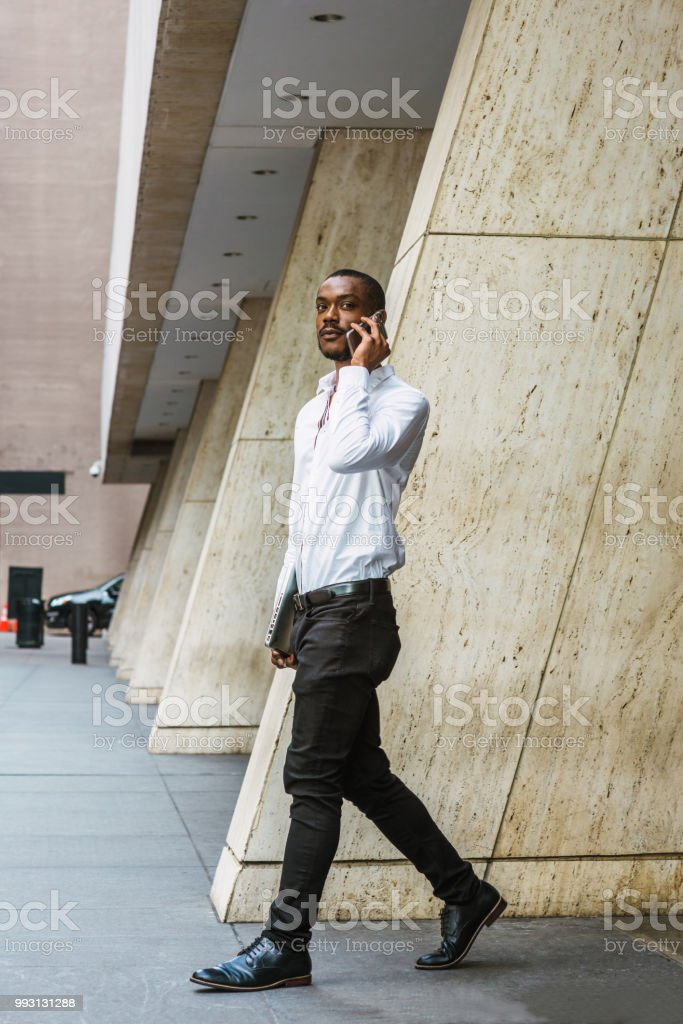 82d9e70e98 Young African American businessman with beard talking on cell phone,  traveling in New York - Stock image .