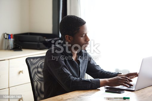 istock young african american businessman working on laptop computer in office 1036091750
