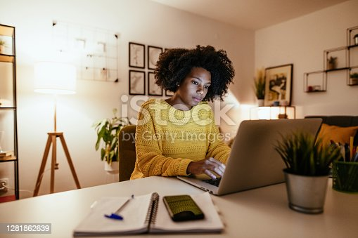 Young African American woman at home, dressed in casual sweater and working or studying.