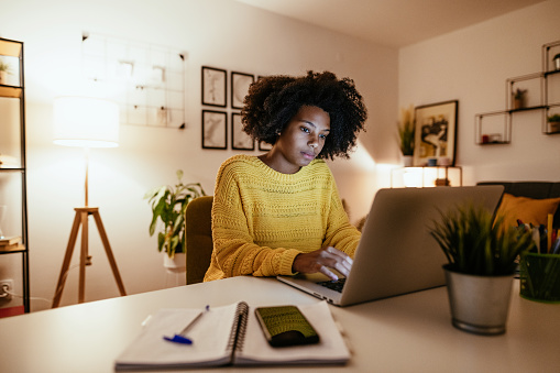 Young African American businesswoman at home office, working late