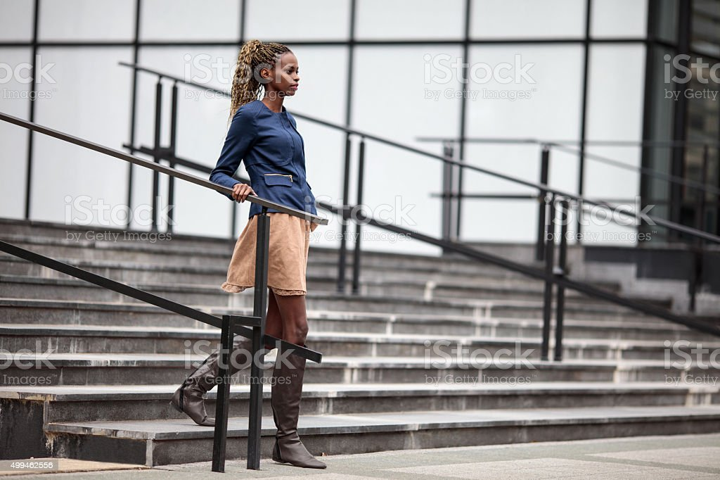 Young African American businesswoman moving down the stairs. stock photo