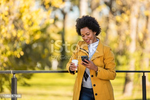 Happy mid adult African American woman text messaging on phone while on a coffee break.