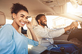Young african american couple driving in car, travelling together by auto