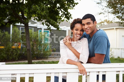 Young African American couple embrace outside their house