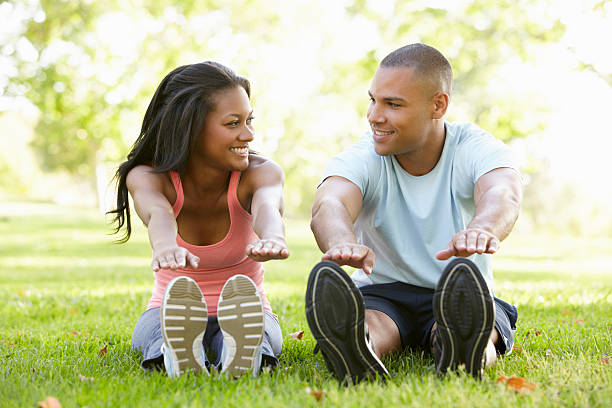 A young African American couple exercising in a park Young African American Couple Exercising In Park Stretching To Touch Their Toes touching toes stock pictures, royalty-free photos & images