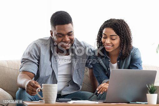 1174436608 istock photo Young african american couple planning budget together at home, writing notes to notebook, creating checklist for shopping or guest list for wedding 1226384618