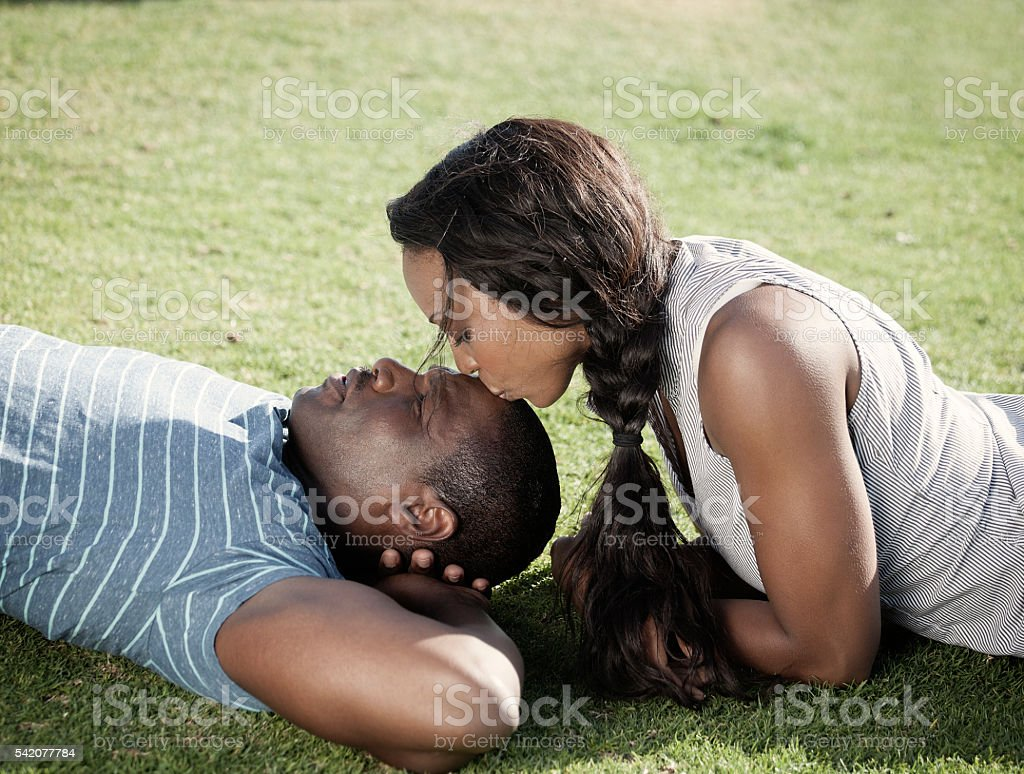 Young African American couple relaxing on the grass stock photo