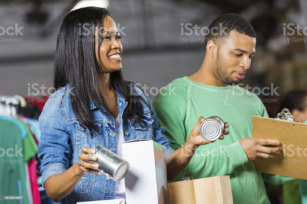 Young African American couple sorting grocery donations at food bank stock photo