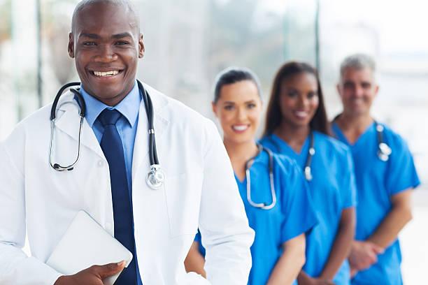 jeune médecin africain-américain et vos collègues - vêtements professionnels hospitaliers photos et images de collection
